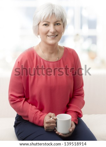 Close-up portrait of a beautiful senior woman enjoying a cup of tea or coffee. - stock photo