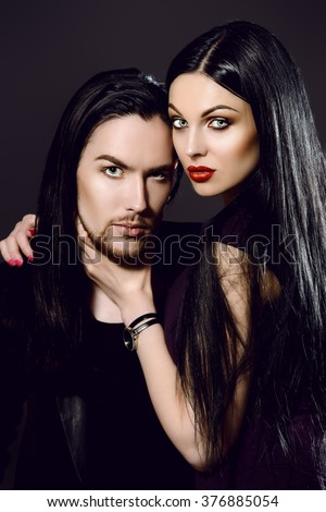 Close-up portrait of a beautiful sexual couple in black clothes. Fashion, glamour. Black background.