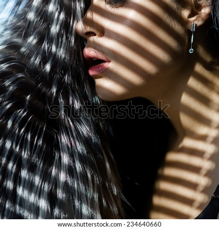 Close-up portrait of a beautiful sexy girl in profile, the sun through the blinds - stock photo