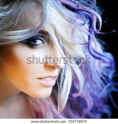 close-up portrait of a beautiful sexy young blonde girl hipster with lilac and pink hair on the background of blooming lilacs, posing and with bright makeup - stock photo
