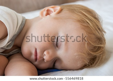 close-up portrait of a beautiful sleeping baby on bed.