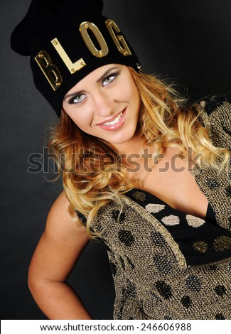 close up portrait of a beautiful smiling caucasian girl with long curly hair wearing a funny blog hat isolated on black background - stock photo
