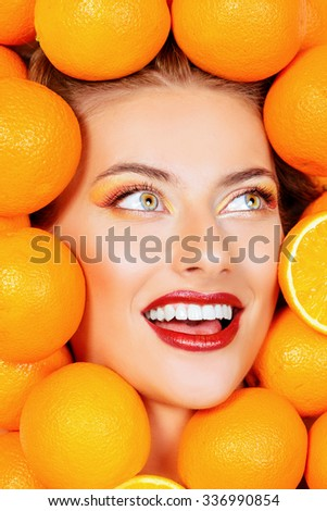 Close-up portrait of a beautiful smiling woman among fresh oranges. Healthy eating, juice. Make-up, cosmetics. Healthy teeth. - stock photo