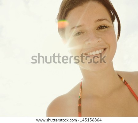 Close up portrait of a beautiful teenager woman wearing a red bikini and standing on an urban beach with city buildings, smiling and looking at the camera on vacation with the sun rays flare. - stock photo