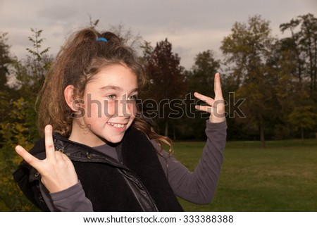Close up portrait of a beautiful ten years old little girl in autumn park - stock photo