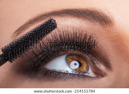 Close-up portrait of a beautiful woman applying mascara for eyelashes - stock photo