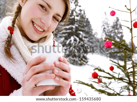 Close up portrait of a beautiful woman in the snow mountains, celebrating christmas with a decorated xmas tree in nature and holding a hot cup of tea or coffee beverage, smiling outdoors. - stock photo