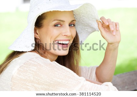 Close up portrait of a beautiful woman laughing with sun hat - stock photo