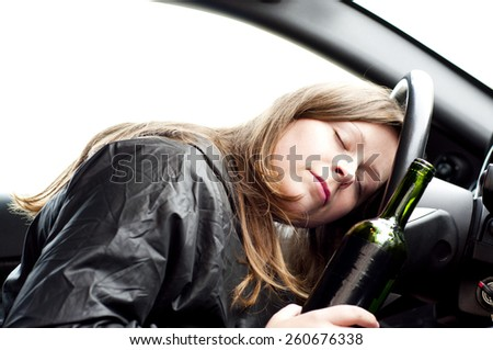 Close up portrait of a beautiful woman lying asleep on the steering wheel drunk after drinking alcohol, do not drink and drive concept - stock photo
