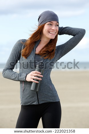 Close up portrait of a beautiful woman smiling with water bottle outdoors - stock photo