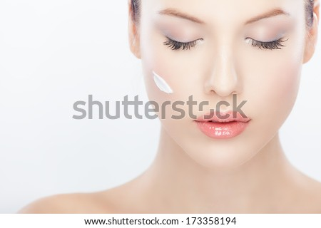 Close-up portrait of a beautiful woman with cream on her face  - stock photo