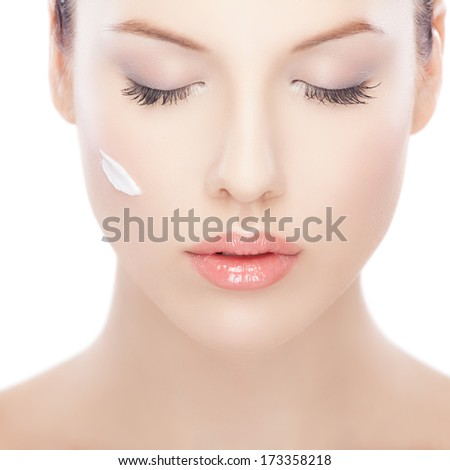 Close-up portrait of a beautiful woman with skin lotion on her face  - stock photo