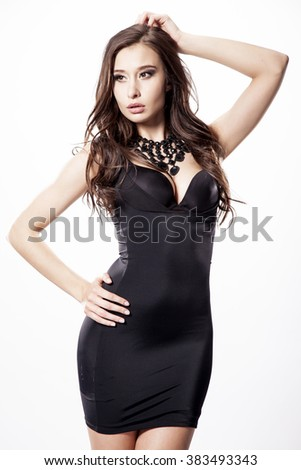 Close up portrait of a beautiful young adult slim sexy and attractive sensuality pretty brunette woman in black elegance fashionable dress isolated on white background