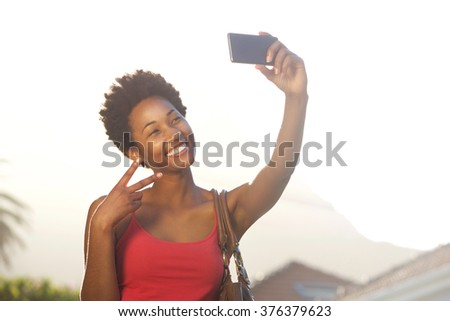 Close up portrait of a beautiful young african woman gesturing peace sign while taking a selfie