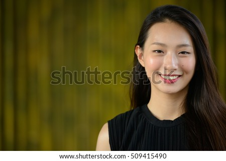 Close up portrait of a beautiful young Asian businesswoman smiling and looking at camera