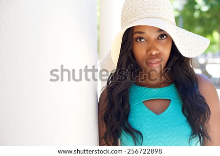Close up portrait of a beautiful young black woman in sun hat - stock photo
