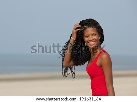 Close up portrait of a beautiful young black woman smiling at the beach  - stock photo