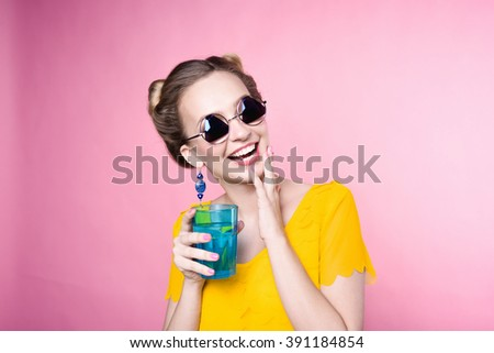 close-up portrait of a beautiful young blonde girl in fashionable sunglasses on a pink background in the studio in a yellow blouse with a blue glass cup of water in his hands with nail polish smiling