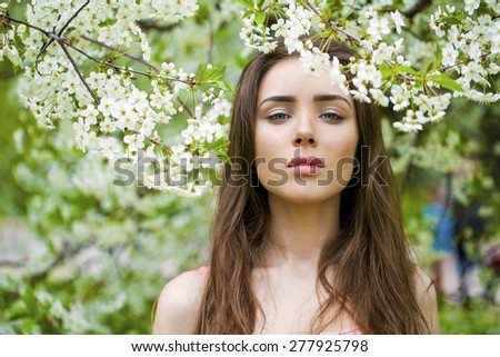 Close up portrait of a beautiful young brunette woman on the background of the cherry blossoms, spring park - stock photo