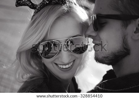 close-up portrait of a beautiful young couple in love bright blonde girl with and a guy with a beard wearing a cap hipsters on a background smiling and posing lifestyle  in jeans - stock photo