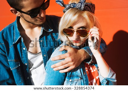 close-up portrait of a beautiful young couple in love bright blonde girl with red lips and a guy with a beard wearing a cap hipsters on a red background smiling and posing lifestyle  in jeans - stock photo