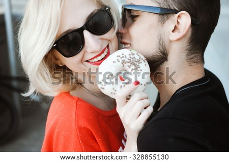close-up portrait of a beautiful young couple in love bright blonde girl with red lips and a guy with a beard wearing a cap hipsters  yellow background smiling and posing lifestyle   donut, eat - stock photo