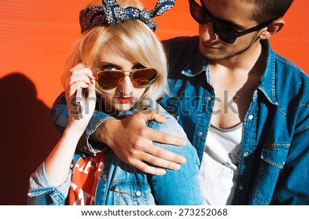close-up portrait of a beautiful young couple on a sunny day, hipsters, girl blonde with red lips and wearing sunglasses and attractive guy with a beard  a denim jacket - stock photo