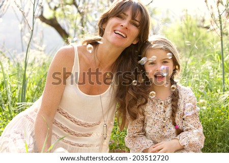 Close up portrait of a beautiful young daughter and her attractive young mother relaxing together in a green garden having fun blowing bubbles on a sunny holiday outdoors. Family activities lifestyle. - stock photo