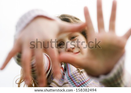 Close up portrait of a beautiful young girl holding her hands in front of her face framing a picture with her fingers, smiling against the sky during a winter day outdoors. - stock photo