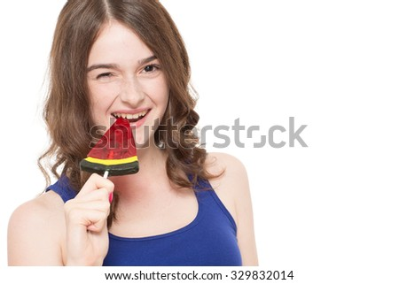 Close up portrait of a beautiful young girl smiling and biting a watermelon lollipop ,isolated on white background - stock photo