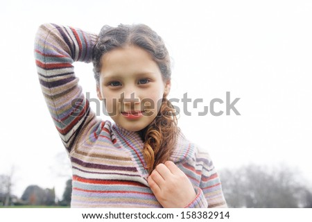 Close up portrait of a beautiful young girl with a gentle smiling expression, wearing a stripy knitted jumper and holding her hair up against the sky while in a park during winter day. - stock photo