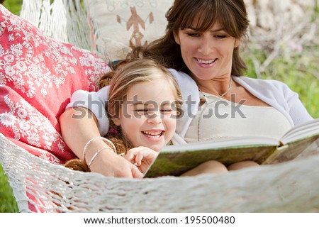 Close up portrait of a beautiful young mother and her five years old daughter laying down in a hammock playfully reading a children stories book during a sunny summer day. Family lifestyle outdoors. - stock photo