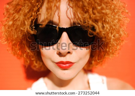 close-up portrait of a beautiful young red-haired curly girl in black sunglasses and red lips on cock background on a sunny day