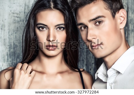 Close-up portrait of a beautiful young woman and a man. Fashionable couple posing at studio.  - stock photo