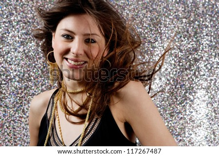 Close up portrait of a beautiful young woman dancing at a party against a silver glitter background.