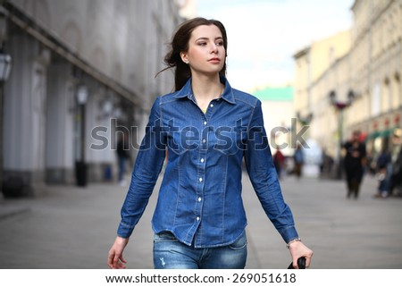 Close up Portrait of a beautiful young woman in a blue jeans shirt on the background of spring street - stock photo