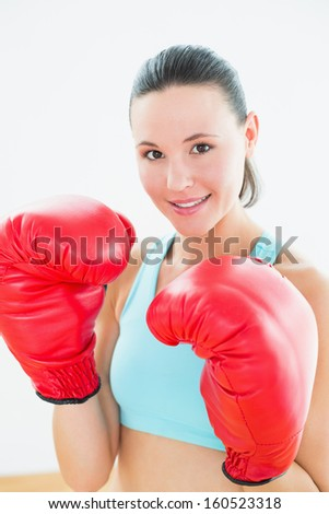 Close-up portrait of a beautiful young woman in red boxing gloves at fitness studio