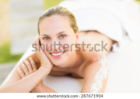 Close up portrait of a beautiful young woman on massage table over white background