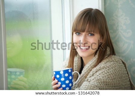 Close up portrait of a beautiful young woman smiling with cup of tea - stock photo
