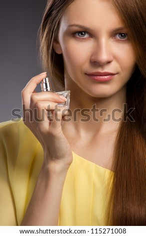 Close up portrait  of a beautiful young woman spraying perfume on gray dark background - stock photo