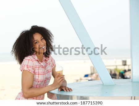 Close up portrait of a beautiful young woman standing outdoors with ice cream - stock photo