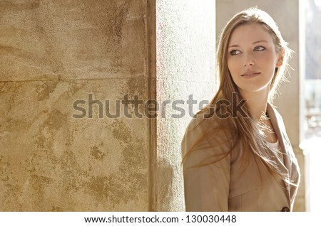 Close up portrait of a beautiful young woman tourist visiting a destination city and leaning on an old textured column with the sun shining behind her, smiling. - stock photo