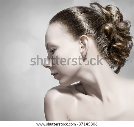 Close-up portrait of a beautiful young woman with a extremely clear skin in profile.