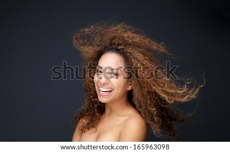 Close up portrait of a beautiful young woman with curly hair laughing - stock photo