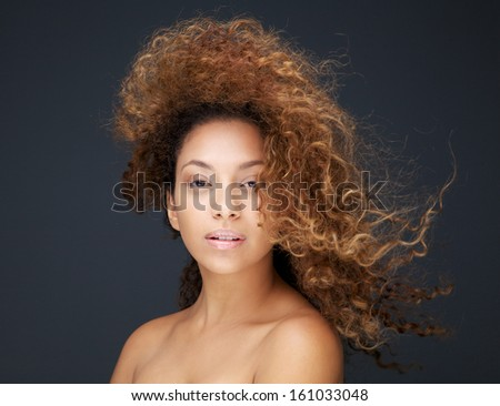 Close up portrait of a beautiful young woman with hair blowing - stock photo