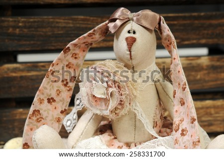 close up portrait of a beige and pink  handmade linen rabbit in vintage style and spring mood - stock photo
