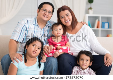 Close-up portrait of a big friendly family smiling and looking at camera  - stock photo