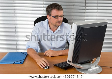 Close-up portrait of a black and grey haired man with computer at desk