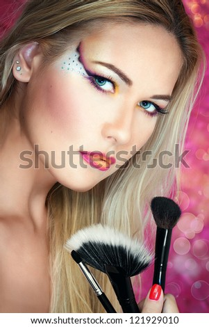 Close up portrait of a blonde girl holding brushes