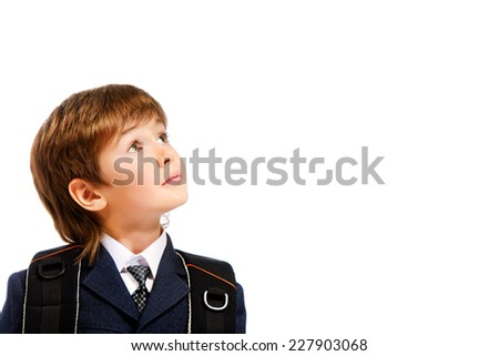 Close-up portrait of a boy in a suit looking up dreamily. Education. Copy space. Isolated over white. - stock photo